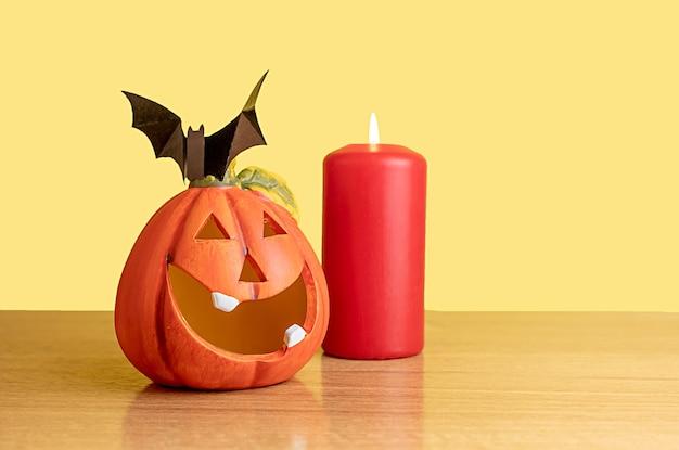 Uma abóbora laranja e uma vela vermelha ficam sobre uma mesa com um fundo amarelo. há um morcego preto na abóbora. feriado de halloween.