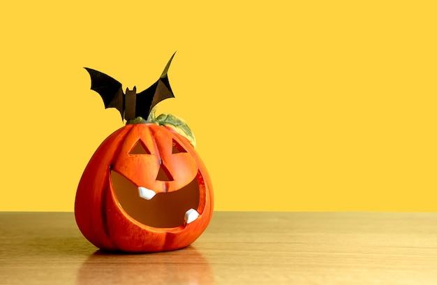 Uma abóbora laranja fica em uma mesa sobre um fundo amarelo. há um morcego preto na abóbora.