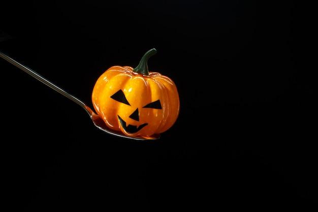 Uma abóbora tradicional de halloween com uma caneca com presas assustador em uma colher de metal no fundo preto