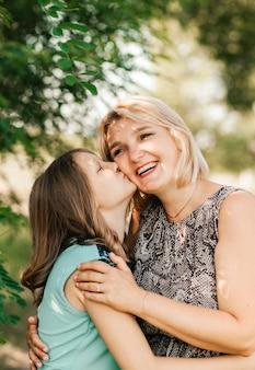 Uma adolescente beija a mãe na bochecha na natureza no verão