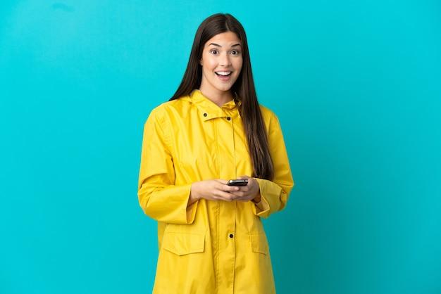 Uma adolescente brasileira vestindo um casaco à prova de chuva sobre um fundo azul isolado surpresa e enviando uma mensagem