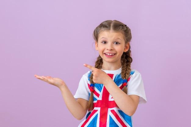Uma adolescente com a imagem da bandeira da grã-bretanha em sua camiseta aponta o dedo para o lado.