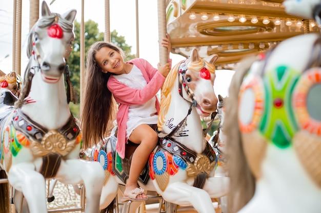 Uma adolescente com cabelo comprido rola em um carrossel de cavalos de balanço. sentado em um cavalo em um parque de diversões