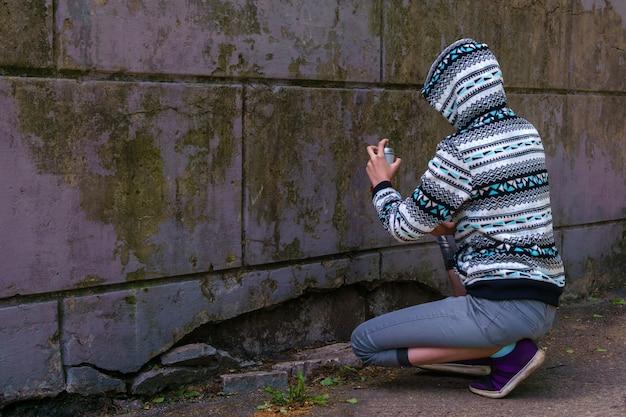 Uma adolescente com tinta spray vai escrever graffiti na parede