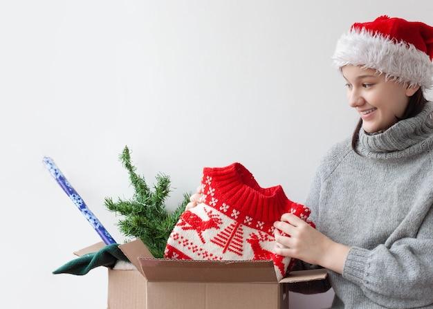 Uma adolescente com um chapéu de papai noel tira um suéter de natal de uma caixa de papelão