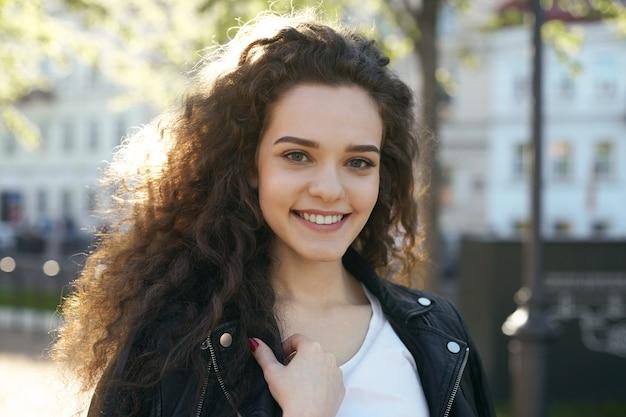 Uma adolescente com um penteado ondulado posando