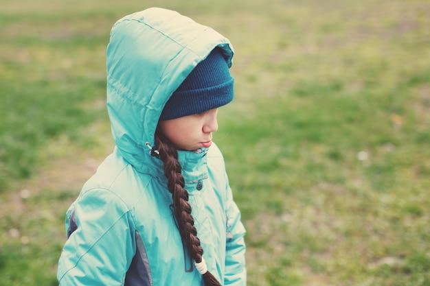 Uma adolescente com uma longa trança em uma jaqueta azul com capuz caminha no gramado.