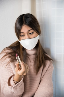 Uma adolescente com uma máscara protetora no rosto e um batom na mão