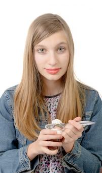 Uma adolescente come um iogurte de chocolate