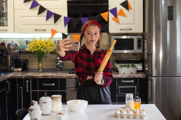 Uma adolescente cozinha para o halloween tirando uma selfie em um telefone celular