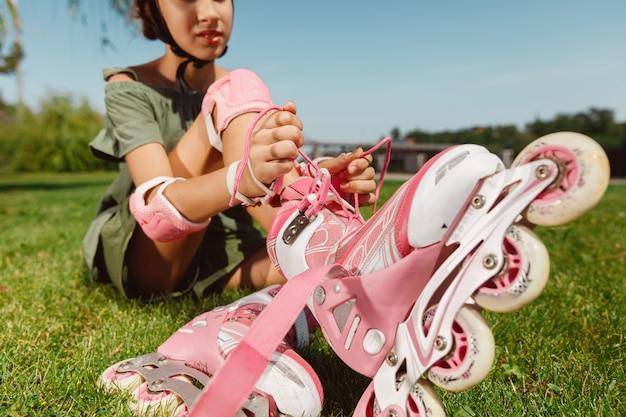 Uma adolescente de capacete aprende a andar de patins segurando o equilíbrio ou patinando e girando nas ruas da cidade em um dia ensolarado de verão