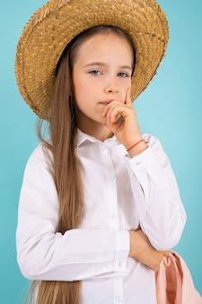 Uma adolescente de olhos cinzentos, sorriso bonito e com um chapéu pensa em algo isolado em fundo azul