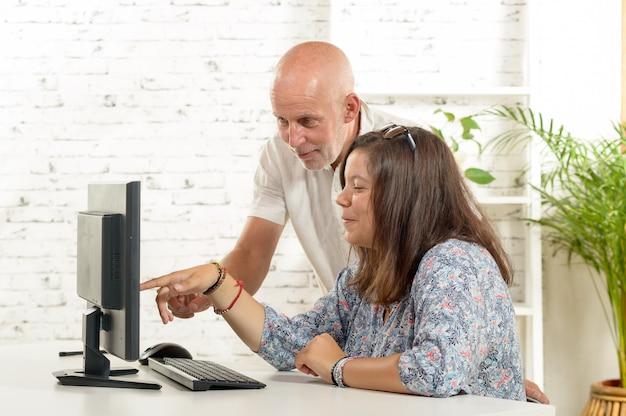 Uma adolescente e seu pai com um computador