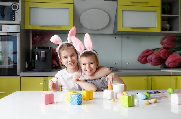 Uma adolescente e um menino com orelhas de coelho na cabeça pintam ovos