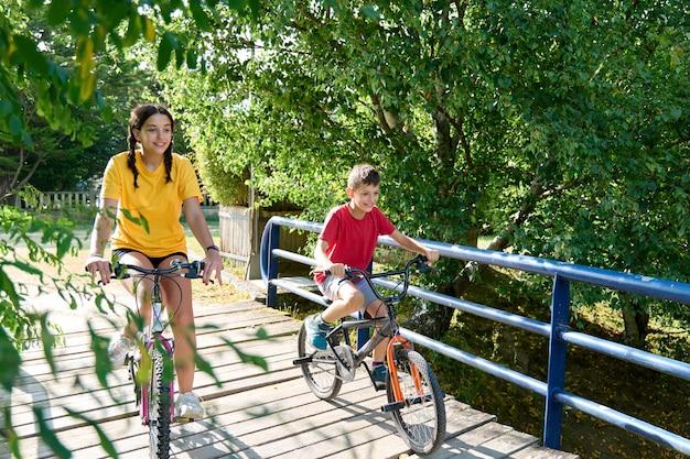 Uma adolescente e um menino de 8 anos andando de bicicleta em um dia ensolarado