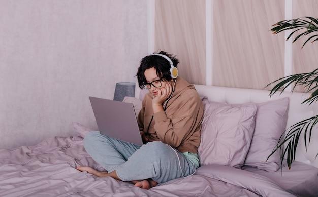 Uma adolescente está sentada em uma cama com um laptop e fazendo a lição de casa