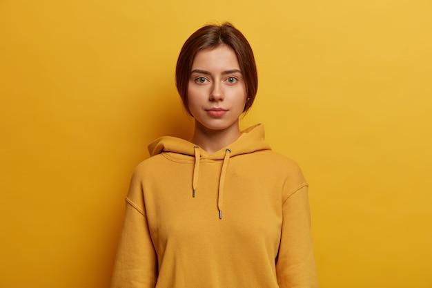 Uma adolescente europeia calma, séria, de olhos verdes, olha com seriedade, conversa casual, discute os acontecimentos do dia a dia, tem o cabelo liso penteado, usa moletom, isolada sobre uma parede amarela