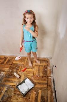 Uma adolescente feliz pintando uma parede em seu quarto