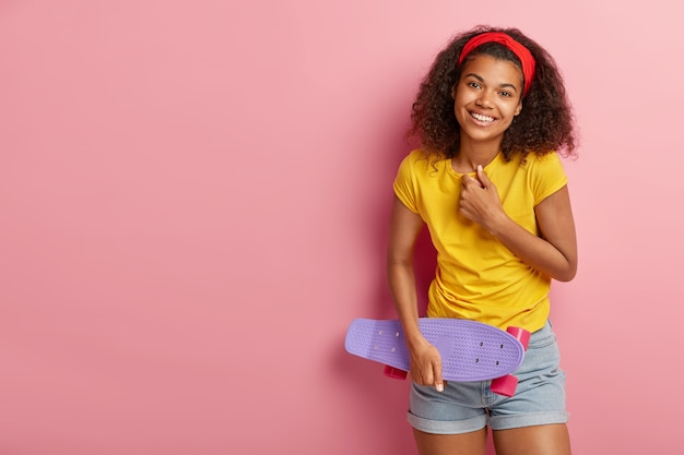 Uma adolescente feliz ri positivamente, está de bom humor, expressa emoções agradáveis, vestida com roupa casual de verão, segura longboard, se diverte com os amigos