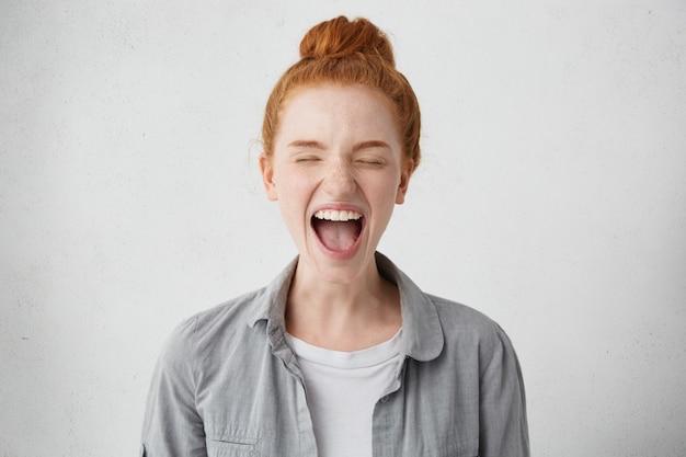 Uma adolescente mimada e travessa com cabelo ruivo entrou em choque, fechando os olhos com força e abrindo a boca em um grito de protesto, desobediência