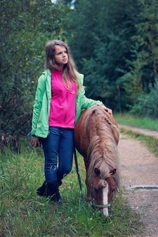 Uma adolescente parada com um cavalinho na beira de uma estrada em uma noite chuvosa de verão