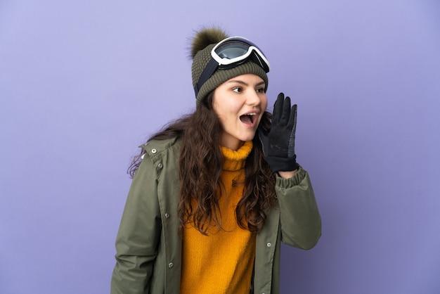 Uma adolescente russa com óculos de snowboard isolada em um fundo roxo gritando com a boca aberta para o lado