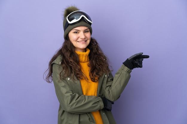 Uma adolescente russa com óculos de snowboard isolados em um fundo roxo apontando o dedo para o lado