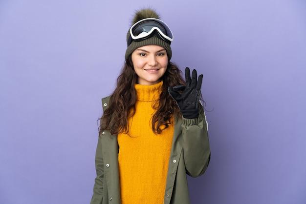 Uma adolescente russa com óculos de snowboard isolados em um fundo roxo, mostrando um sinal de ok com os dedos
