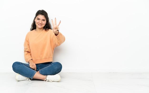 Uma adolescente russa sentada feliz no chão contando três com os dedos