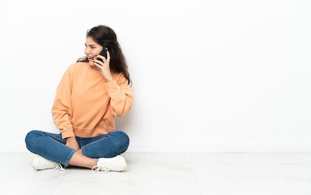 Uma adolescente russa sentada no chão, conversando com alguém ao telefone celular