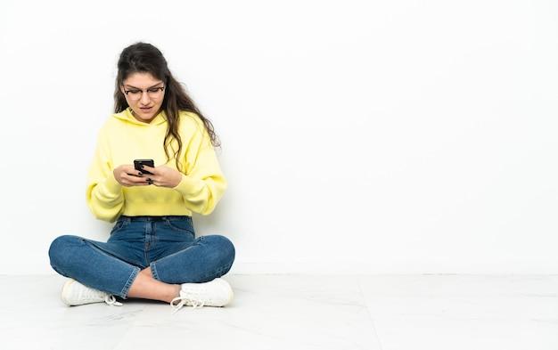Uma adolescente russa sentada no chão enviando uma mensagem com o celular