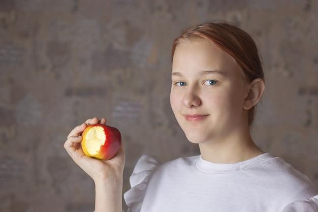 Uma adolescente segurando uma maçã mordida