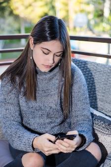 Uma adolescente, sentada em um terraço, olhando para o celular