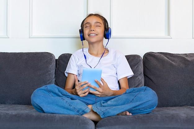Uma adolescente sentada no sofá com um tablet e ouve música com fones de ouvido