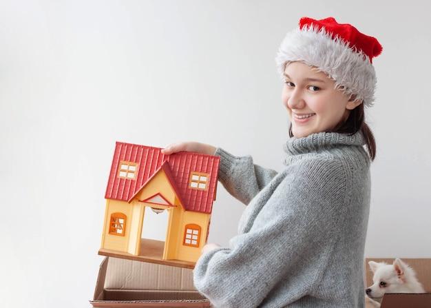 Uma adolescente tira uma casa de brinquedo de uma caixa de papelão.