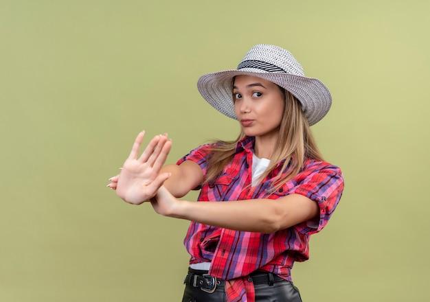 Uma adorável jovem de camisa xadrez mostrando um gesto de parar