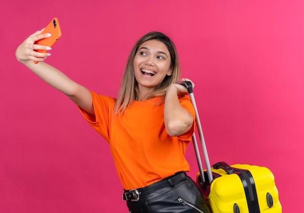 Uma adorável jovem em uma camiseta laranja sorrindo e tirando uma selfie com o celular, segurando uma mala amarela em uma parede rosa