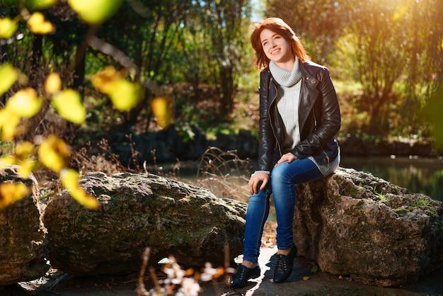 Uma adorável jovem está sentada em uma pedra perto de um lago em um parque de outono ao sol