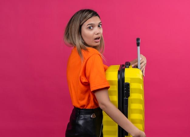 Uma adorável jovem vestindo uma camisa laranja correndo segurando uma mala amarela enquanto olha surpreendentemente para uma parede rosa