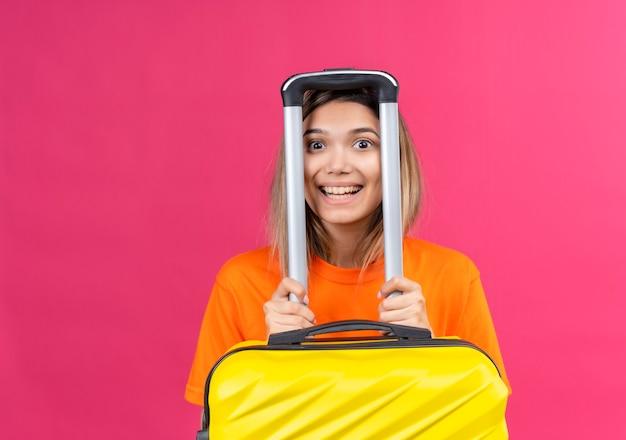 Uma adorável jovem vestindo uma camisa laranja correndo, sorrindo e olhando enquanto segura uma mala amarela em uma parede rosa