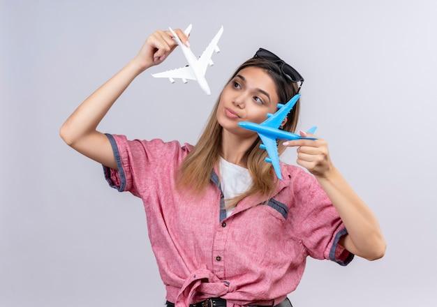 Uma adorável jovem vestindo uma camisa vermelha com óculos de sol, olhando para aviões de brinquedo brancos e azuis enquanto os pilotava em uma parede branca