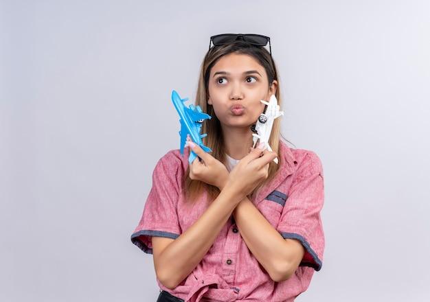 Uma adorável jovem vestindo uma camisa vermelha com óculos escuros olhando para cima enquanto voava em aviões de brinquedo azuis e brancos em uma parede branca