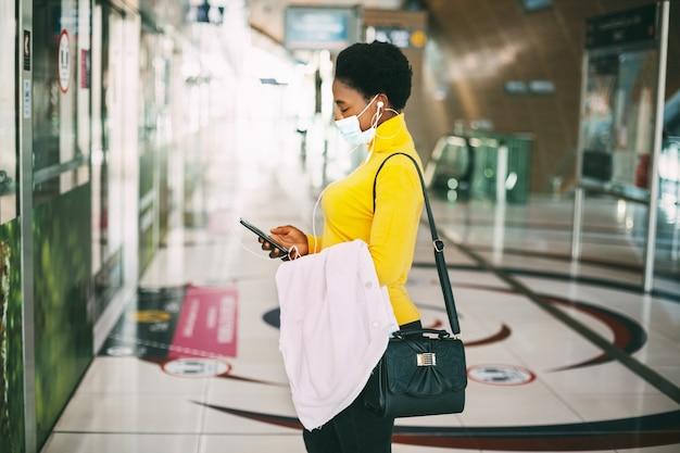 Uma africana com máscara protetora espera a chegada do metrô e ouve música com fones de ouvido. distância social, pandemia.