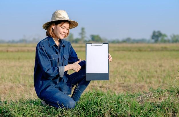 Uma agricultora asiática de jeans senta-se segurando um quadro de notas e sorri no campo com os polegares para cima.