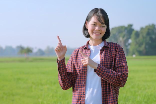 Uma agricultora com uma camisa listrada está posando com o dedo para uma promoção em um campo.