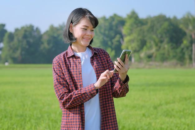 Uma agricultora com uma camisa listrada está posando com um smartphone em um campo.