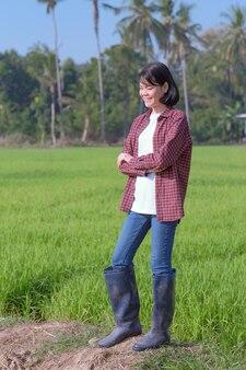 Uma agricultora com uma camisa listrada está sorrindo para um campo verde.