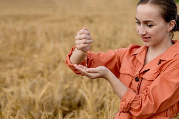 Uma agricultora ou agrônoma está colocando grãos de trigo em suas mãos, colheita madura