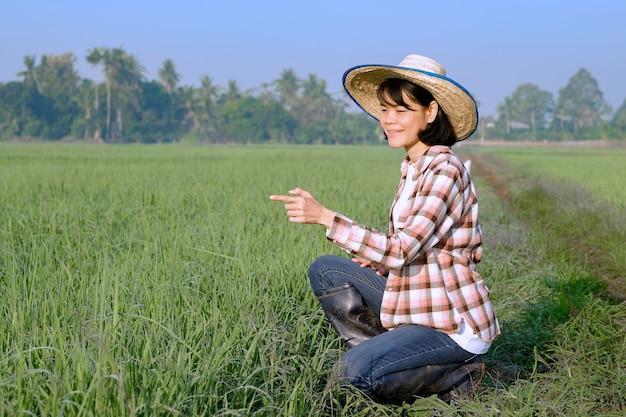 Uma agricultora sentada em um campo posa com um dedo apontando e um rosto sorridente.
