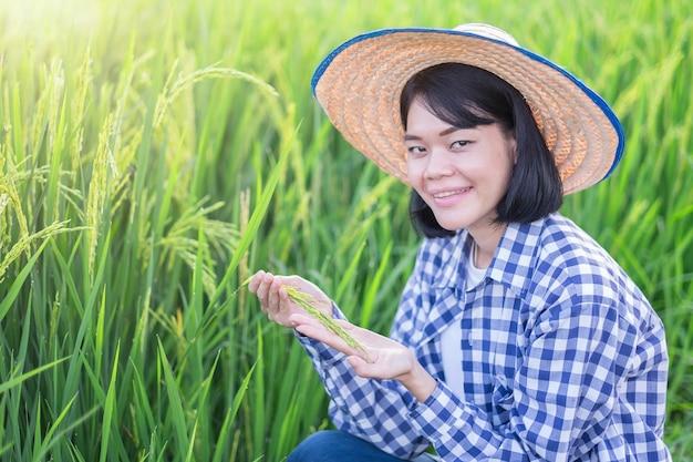 Uma agricultora vestindo uma camisa listrada está sentada com arroz em casca em um belo campo de arroz verde.